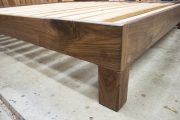 Live-edge walnut slab headboard frame corner