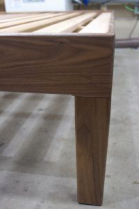 Tapered (on all four sides) leg on a walnut king.